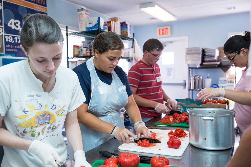Students in campus kitchen cutting tomatoes