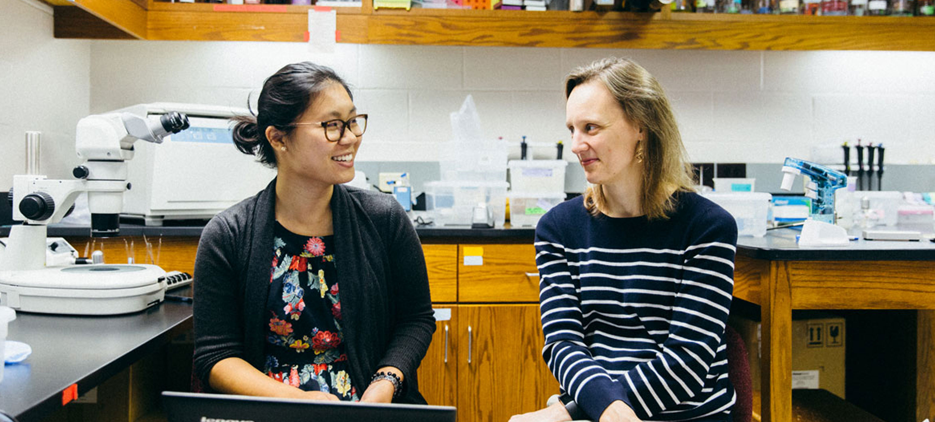 Zoe Yeoh 18 and Biology Professor Jennifer Powell sitting in a lab