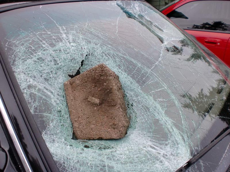 A rock on a broken glass of the front of a car