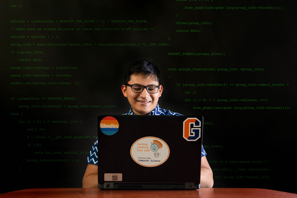 Ricardo Hernandez 21 looking at his laptop in front of a code board