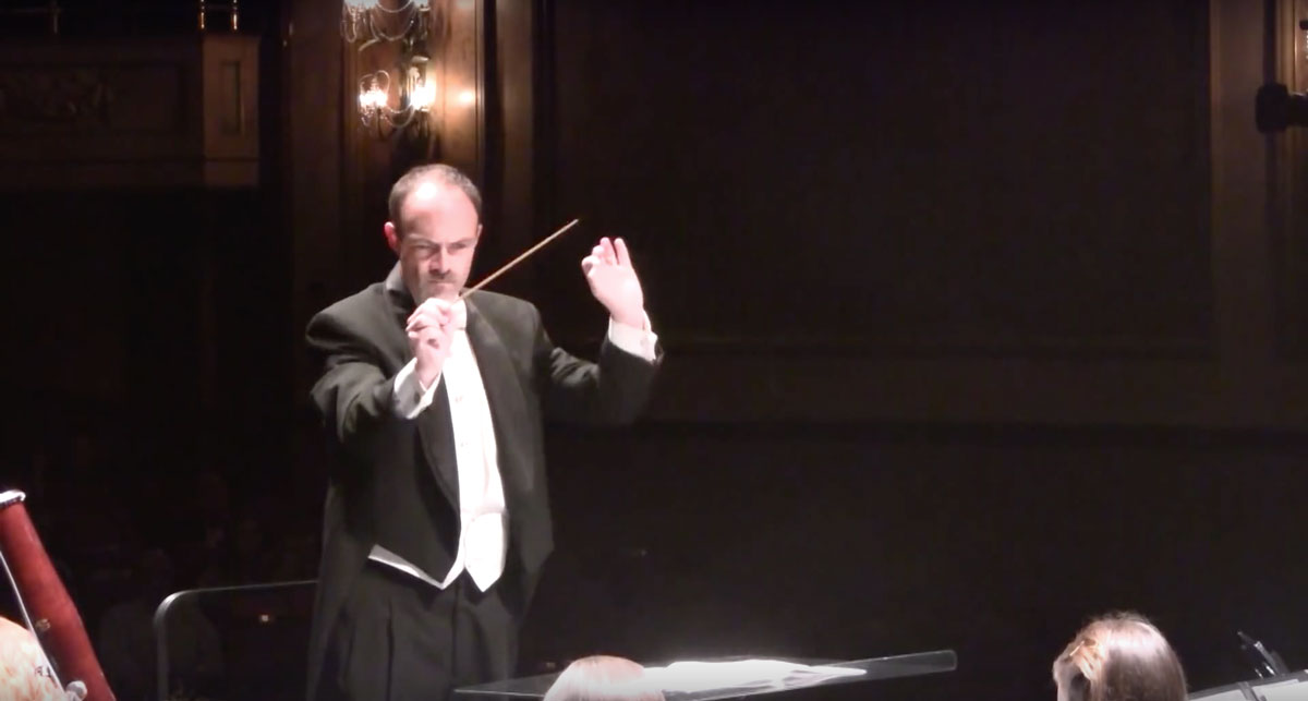 Professor Russell McCutcheon conducting on stage