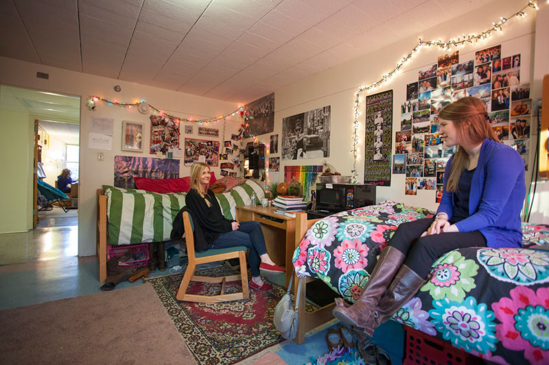 Two female college students inside their dorm room