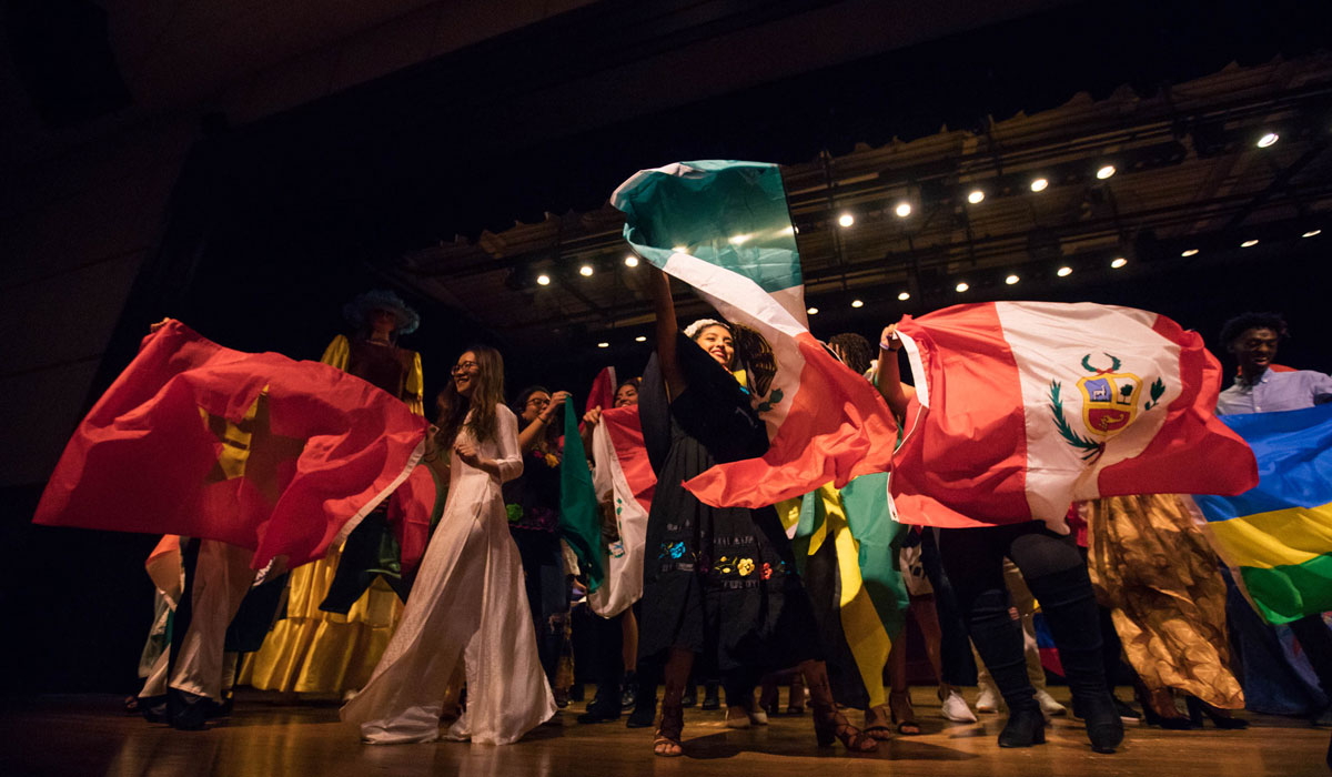 Students wave international flags on stage at BurgBurst