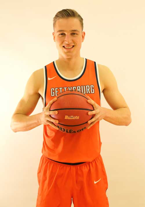 Chris Jack wearing Gettysburg College's basetball uniform holding a basketball