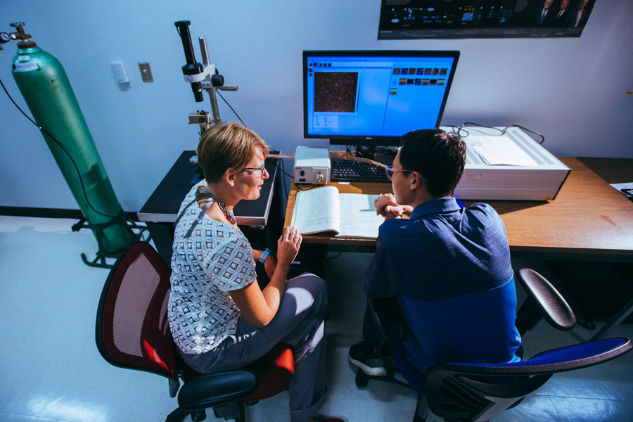 Prof. Shelli Frey working alongside a student with hands-on research.