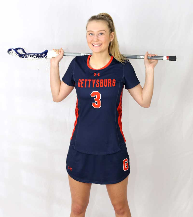 Liza Barr posing in her lacrosse uniform with her lacrosse stick