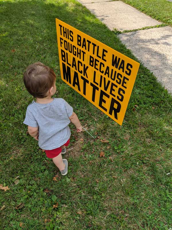 Amanda Heim's young son stands in front of a yard sign in her front yard