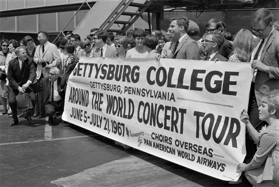 Members of the Gettysburg College Choir holding a banner with language about a world tour