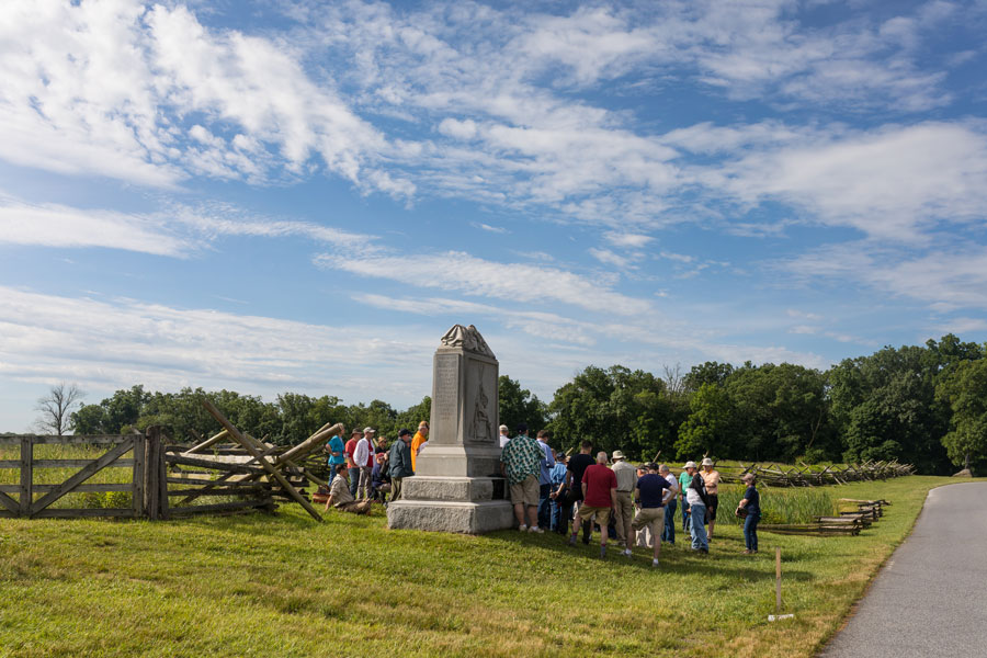 People crowded around a monument on the Gettysburg Battlefield