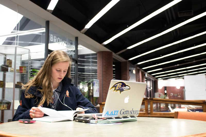 Female student studying with her laptop in the library