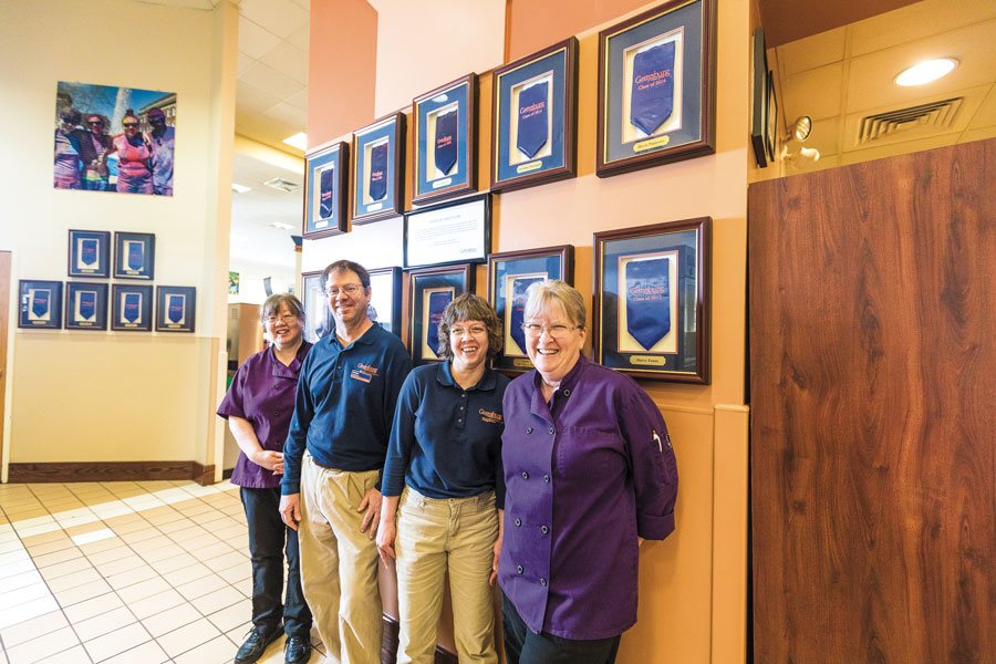 Dining Services employees with stoles of gratitude on the wall