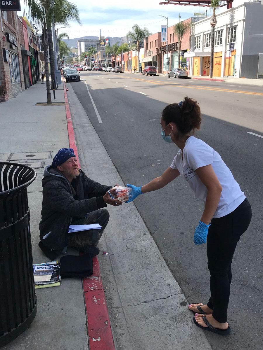 Hamasa Ebadi handing a homeless man a package of food in downtown Los Angeles
