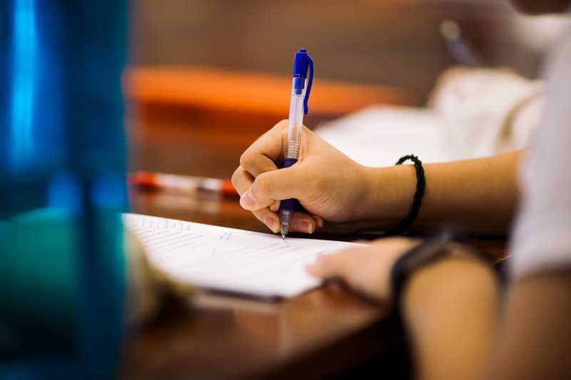 Student's hand writing on a desk