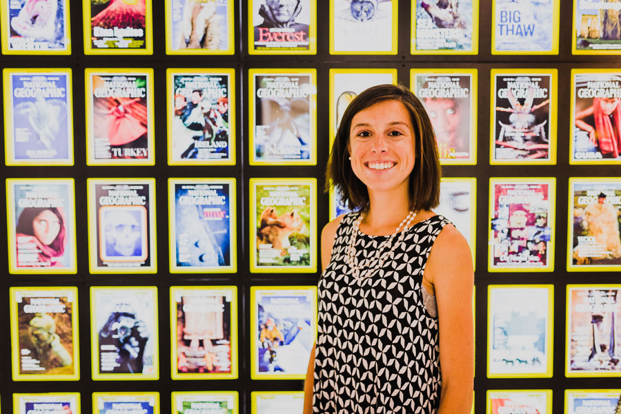 Elizabeth Hilfrank posing in front of an illumnated wall of National Geographic magazine covers