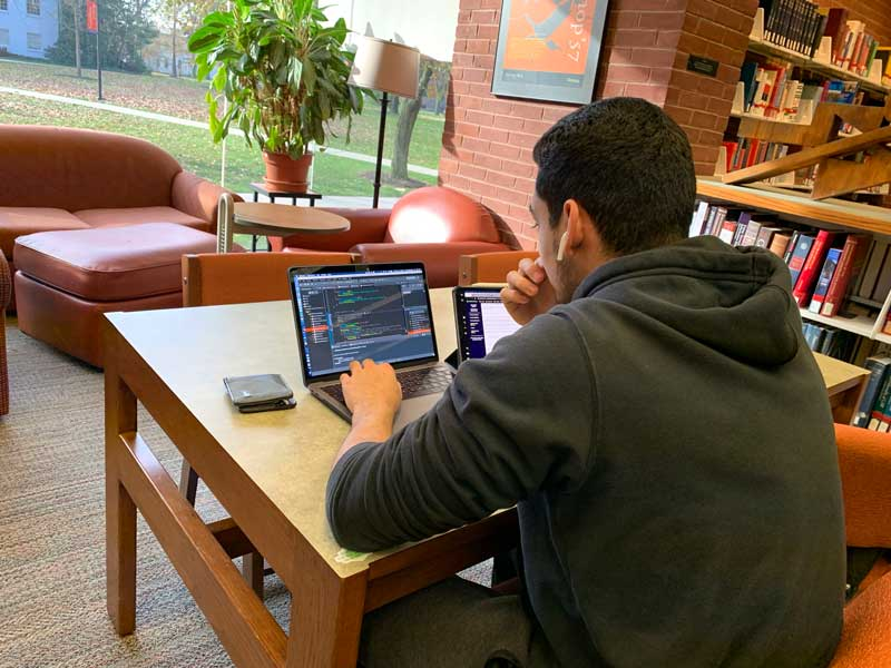 Male student using his laptop to study in the library