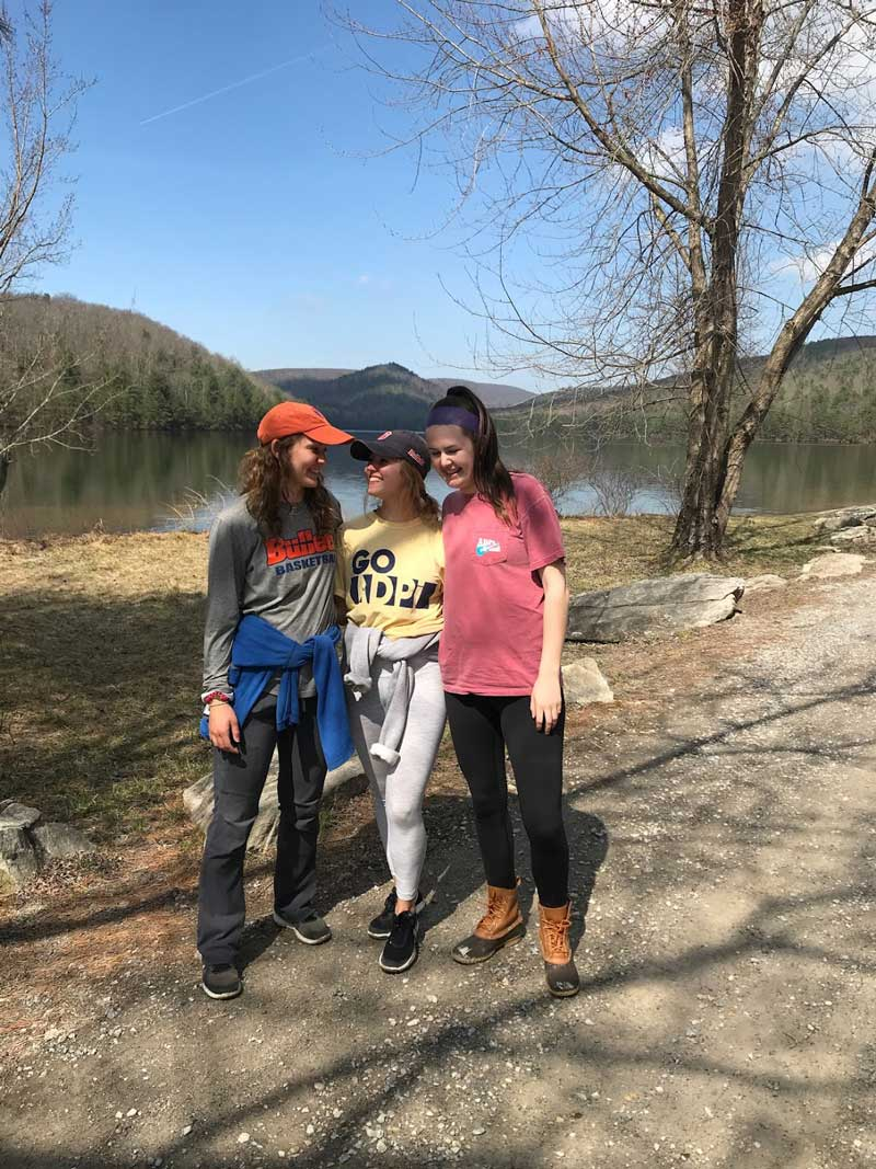 Gabi Eglinton in front of a lake with two other students