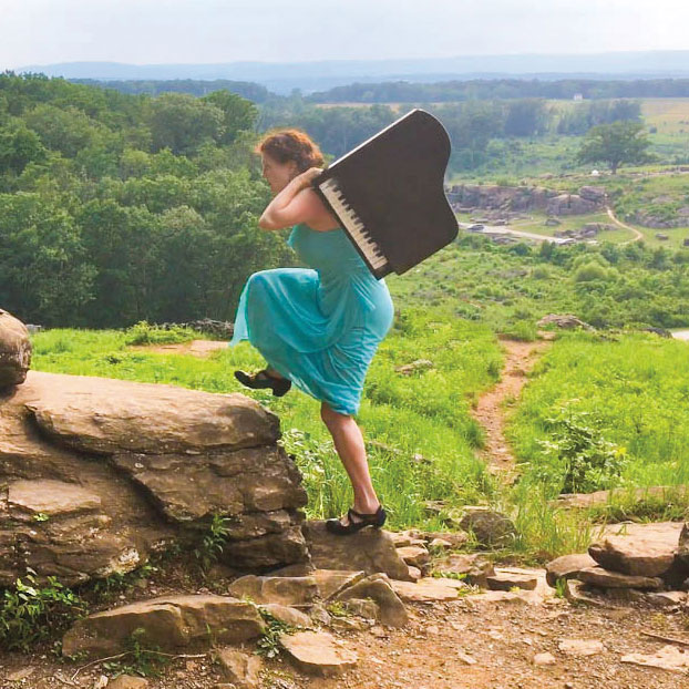 Jocelyn Swigger carrying a small piano on her back on the Gettysburg Battlefield