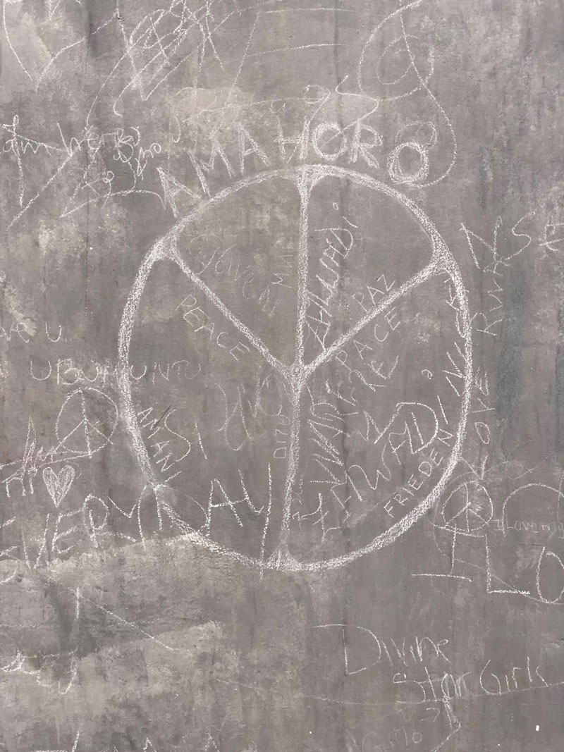 Peace symbol scratched onto a concrete wall