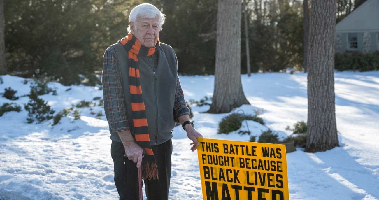 Karl Mattson outside in the winter with a sign that he made