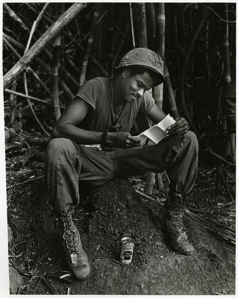 Soldier sitting and reading a letter