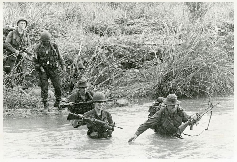 Soldiers fording through a stream in Vietnam