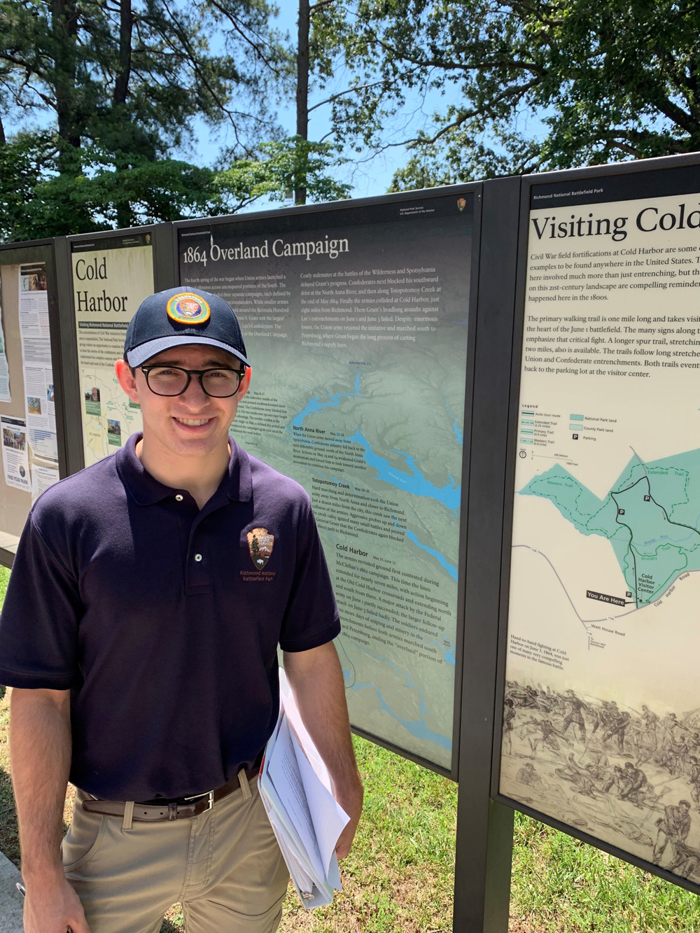 Sean Thompson standing in front of a sign in Cold Harbor National Battlefield Park