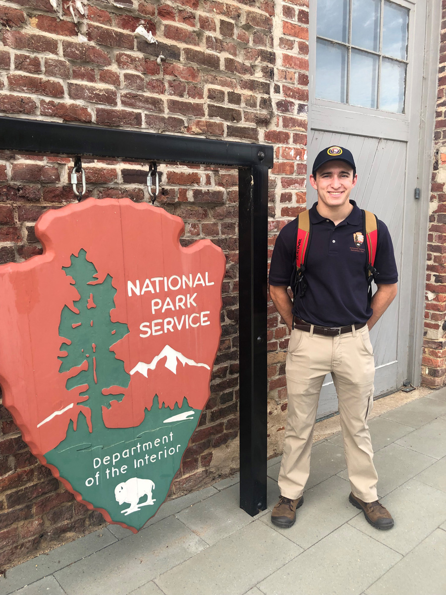 Sean Thompson standing next to a National Park Service sign