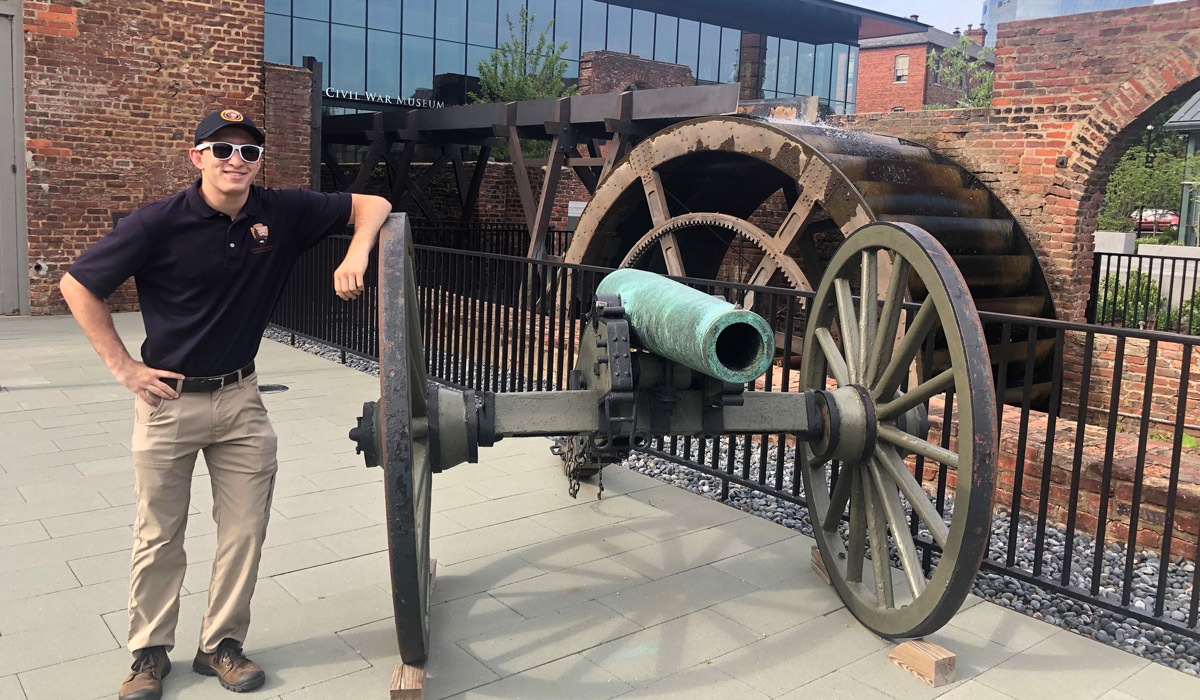 Sean Thompson standing next to a cannon