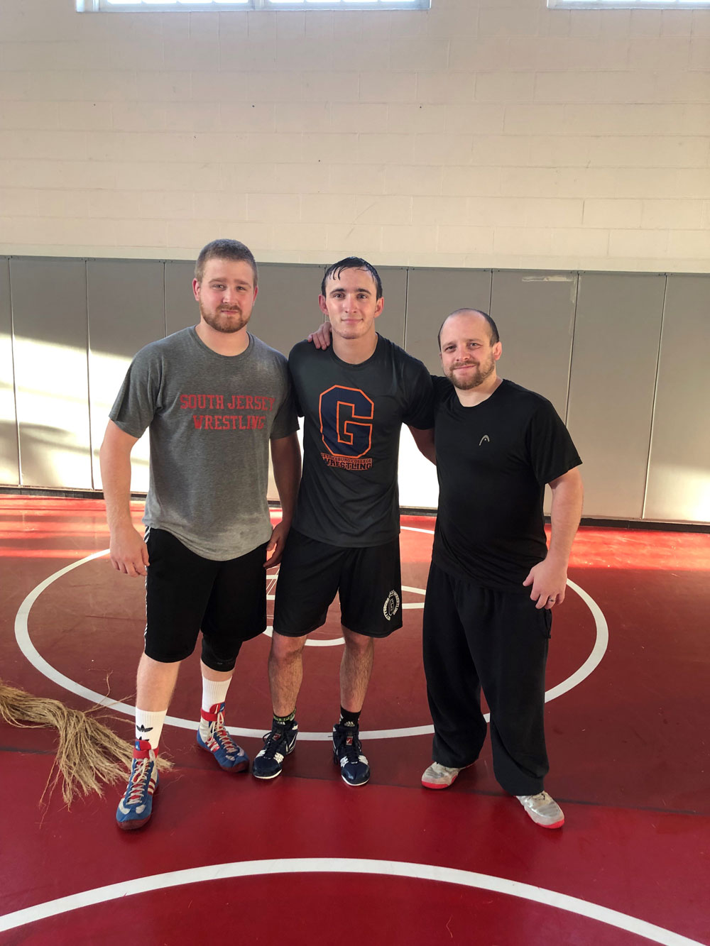 Sean Thompson posing with two other wrestlers in a gym