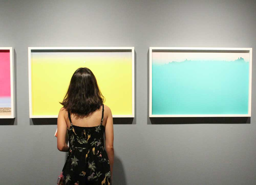 A woman standing in front of three colorful paintings