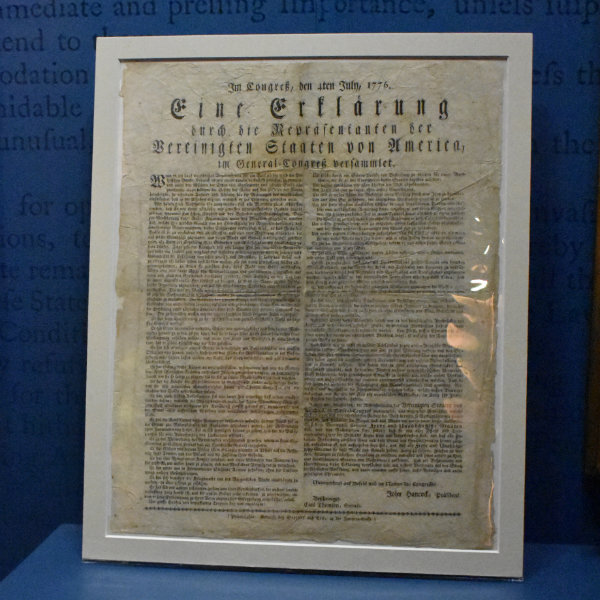 The German-language Declaration of Independence framed and lit for display.