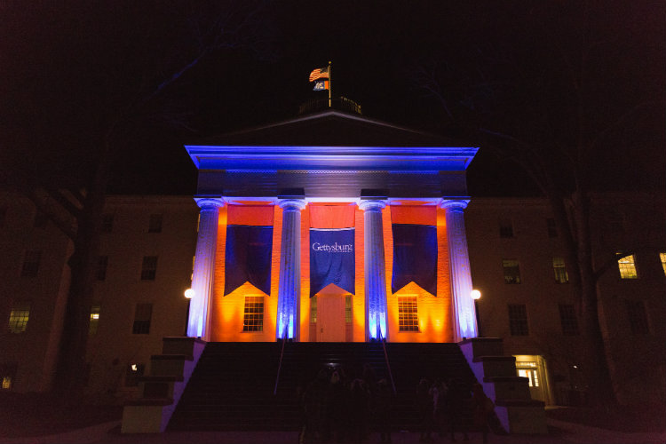 Penn Hall lit up in orange and blue for Twilight Hour.