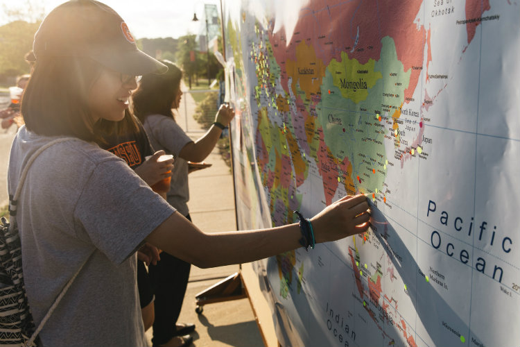 Students mark locations they've been on a map of the world.