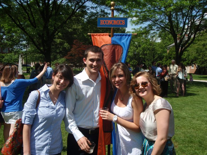 Svet Semov posing with friends and the Economics Department banner during Commencement.