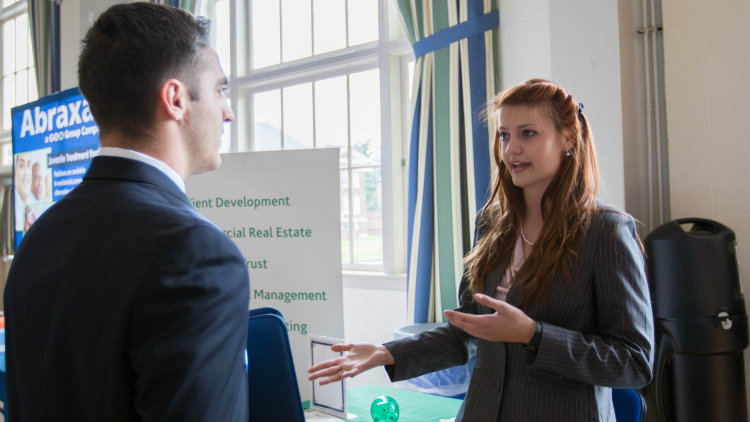 Rachel Fry interacts with a student at a job and internship fair.