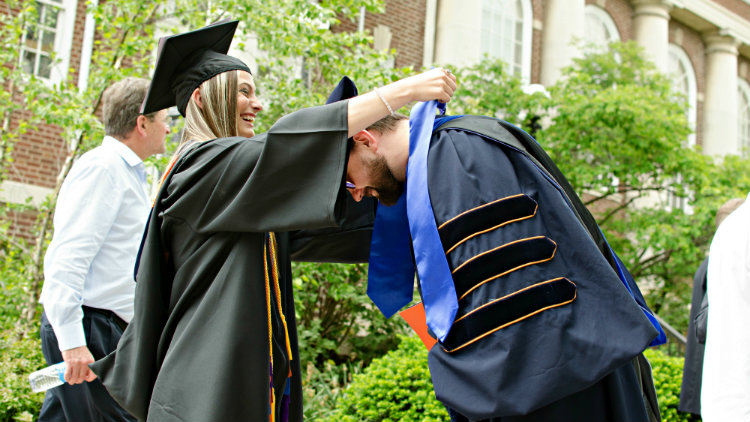 Shannon Brobst giving her Stole of Gratitude to an Economics Professor at Commencement.