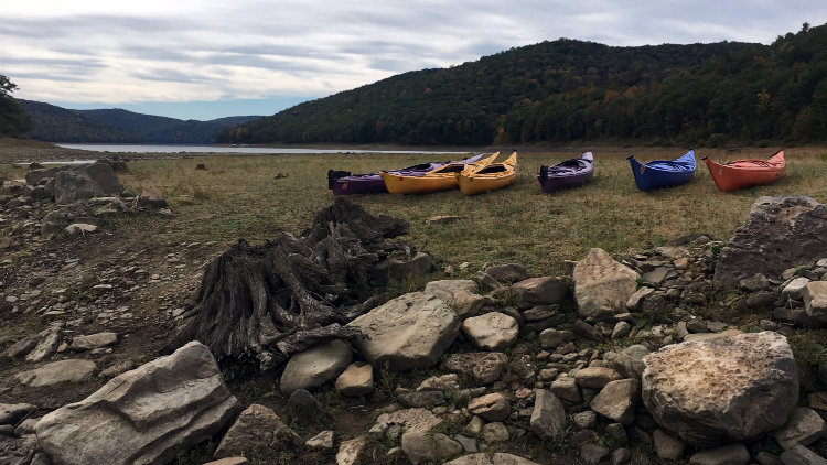 Kayaks lined up on a lake shore for a GRAB trip.