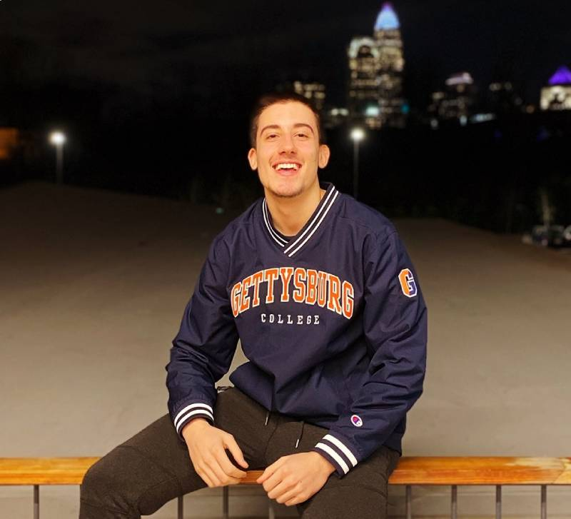 A picture of Tsvetmir sitting on a railing wearing a Gettysburg College jacket smiling at the camera